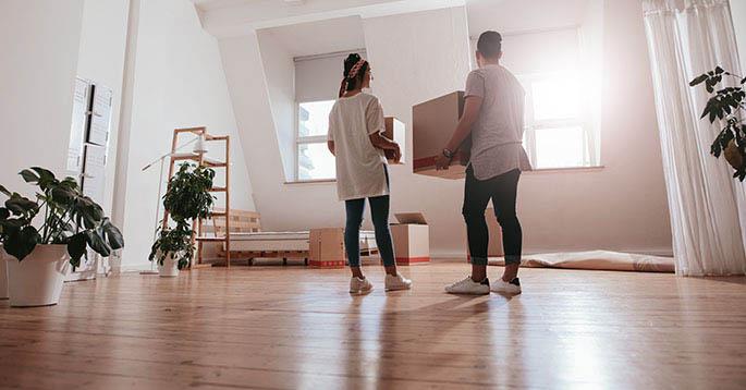 Et par som bærer en flytteeske i en leilighet