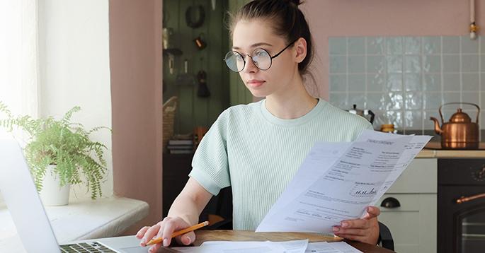 En ung kvinne som ser på en regning ved et skrivebord