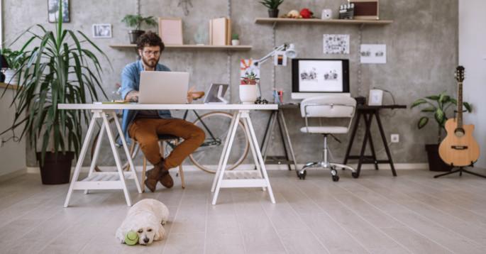 Mann som sitter ved en hjemmepult og jobber på en datamaskin