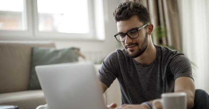 Ung mann ved en bærbar datamaskin