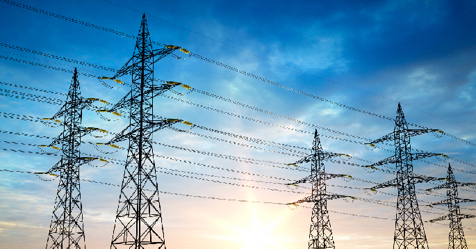 Strømmaster og ledninger mot blå himmel