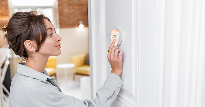 En dame som justerer termostaten på veggen