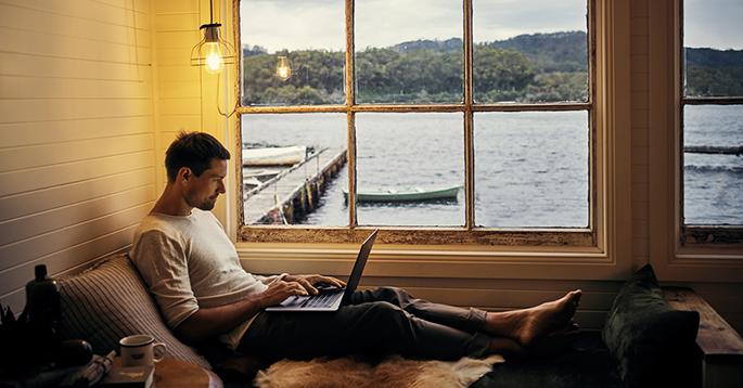 Mann med bærbar datamaskin på hytta