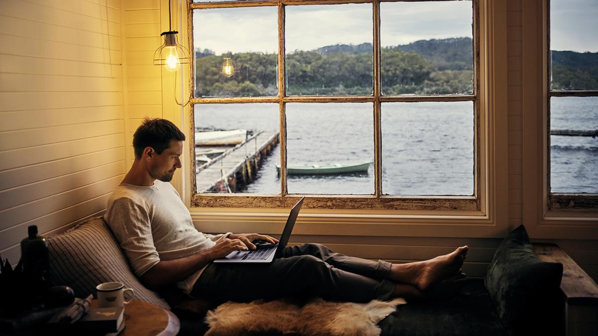 Mann med bærbar datamaskin i på hytta