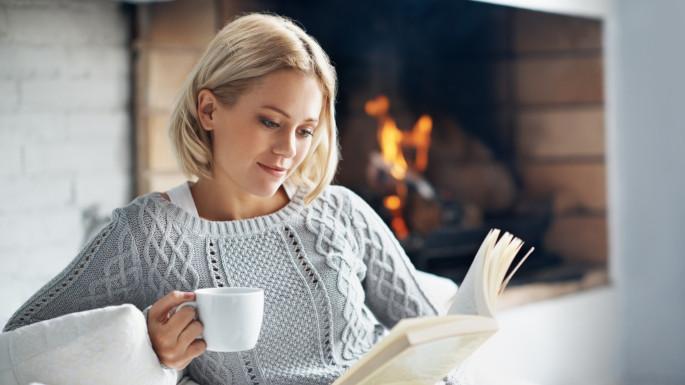 En dame som koser seg med en bok og en kopp kakao foran peisen