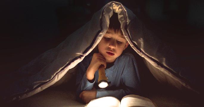 En gutt som leser bok med lommelykt under teppet