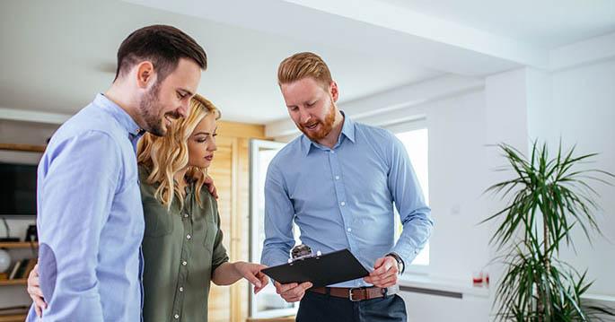 Et par som ser på et skjema med en eiendomsmegler
